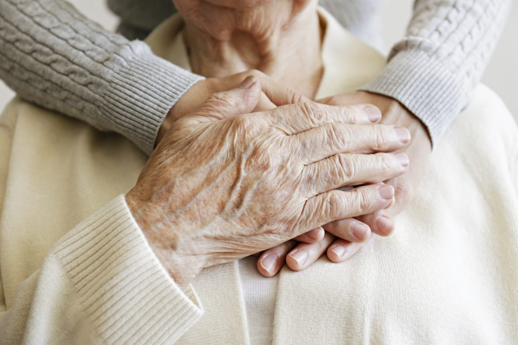 elderly woman and her caregiver's hands